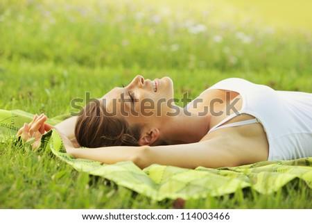 Beautiful woman laying on the grass - stock photo