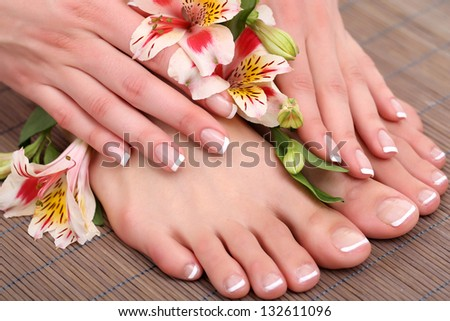 Beautiful woman legs and hands on bamboo mat - stock photo