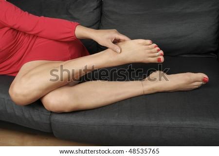 Beautiful woman  legs  massaging aching feet lying - stock photo