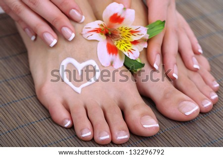 Beautiful woman legs with cream and hands on bamboo mat