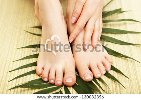 Beautiful woman legs with cream, on bamboo mat - stock photo