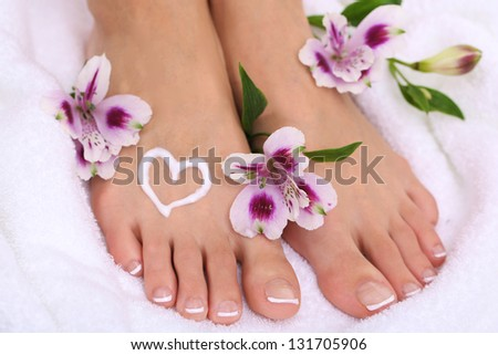 Beautiful woman legs with cream on white towel - stock photo