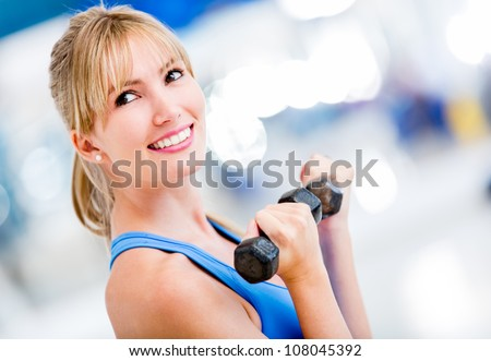Beautiful woman lifting weights at the gym - stock photo