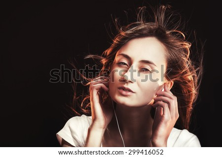 Beautiful Woman Listening Music on a dark background with copy-space. High-contrast image with intentional color shifts