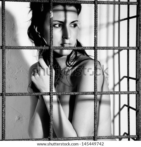beautiful woman locked in a cage with black iron prison or jail bars - stock photo