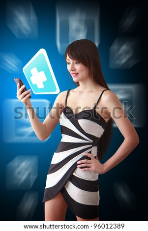 Beautiful woman look at the First Aid icon from mobile phone - stock photo
