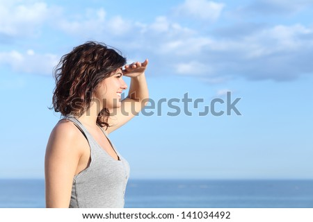 Beautiful woman looking ahead with the hand in forehead and the sea in