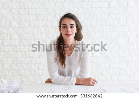Beautiful woman looking at camera free space. Confident female sitting at table and smiling at you, copy space on white bricks background. Success, lifestyle, beauty concept