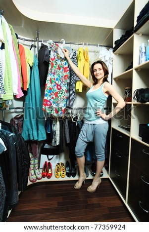Beautiful woman looking at her clothes in a wardrobe at home. - stock photo