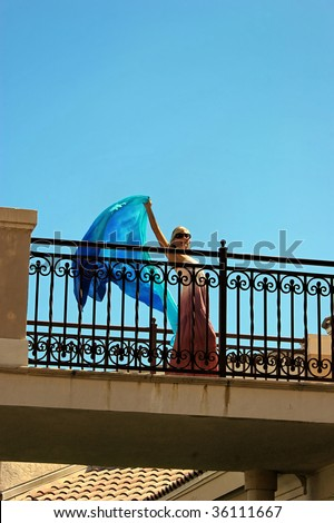 beautiful woman looking down from balcony, waving with long blue cloth in hand. wearing long pink dress and sunglasses with room for text - stock photo