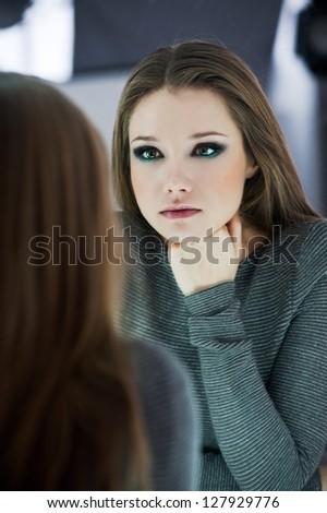 Beautiful woman looking in a mirror - stock photo