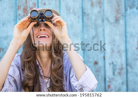 Beautiful woman looking in binoculars up to sky happy smiling. focus on mouth - stock photo