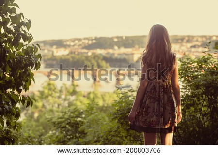 Beautiful woman looking on Prague view panorama from high hill, vintage