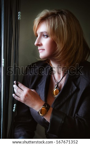 beautiful woman looking out window  - stock photo