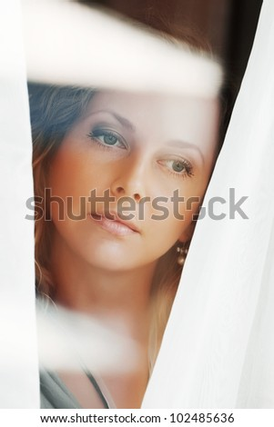 Beautiful woman looking through the window - stock photo