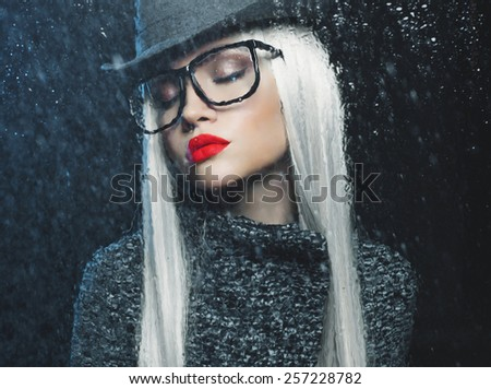 Beautiful woman looking through the window with rain drops - stock photo