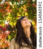 Beautiful woman looking up to autumn leaves - stock photo
