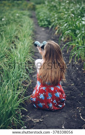 Beautiful woman looking up with binoculars.  Girl with binocular at green grass.  Young woman with binoculars outdoors. Young girl looking through binocular. - stock photo