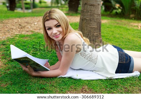 Beautiful Woman Lying Down At The Park Reading Book - stock photo