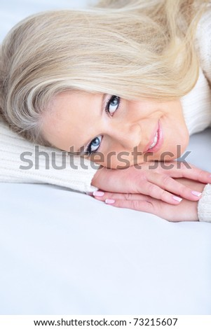Beautiful woman lying down on her bed at home - stock photo