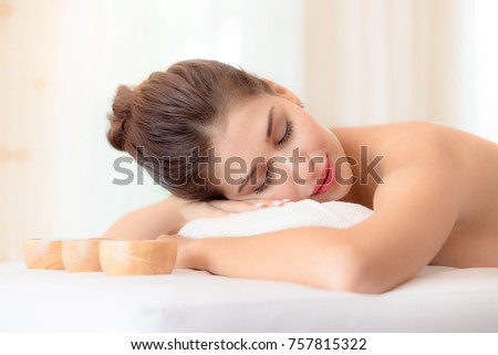 Beautiful woman lying down on the bed relax in spa salon with salt massage.