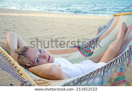 Beautiful woman lying in a hammock on a beach - stock photo
