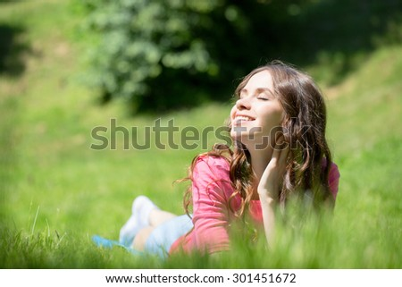 Beautiful woman lying in grass and smiling - stock photo