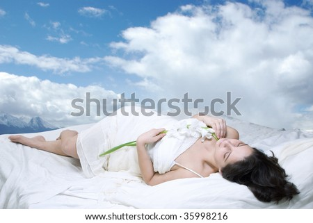 Beautiful woman lying in white bed looking up over cloudy sky background - stock photo