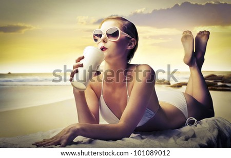 Beautiful woman lying on a bath towel at the seaside and having a refreshing drink - stock photo