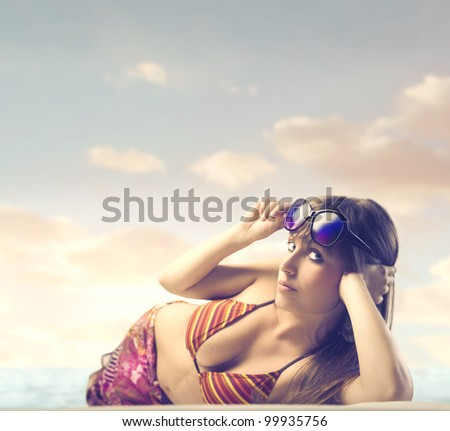 Beautiful woman lying on a beach - stock photo