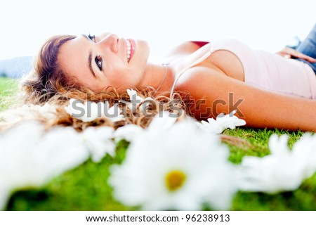 Beautiful woman lying on a garden of flowers and smiling - stock photo
