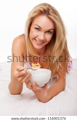 Beautiful woman lying on her stomach on her bed enjoying a healthy breakfast of cereal and fresh milk - stock photo