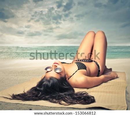 beautiful woman lying on the beach sunbathing - stock photo