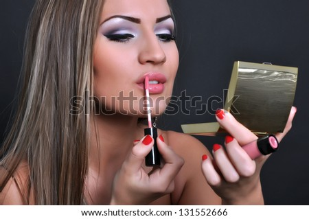 Beautiful woman making her makeup - stock photo