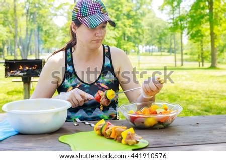 Beautiful woman making shish kebab skewers. - stock photo