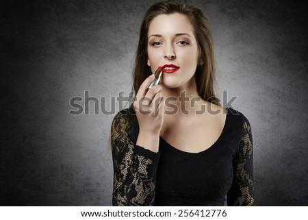 Beautiful woman making up her lips - stock photo