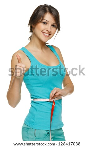Beautiful woman measuring her waist with a measuring tape and showing thumb up, over white background