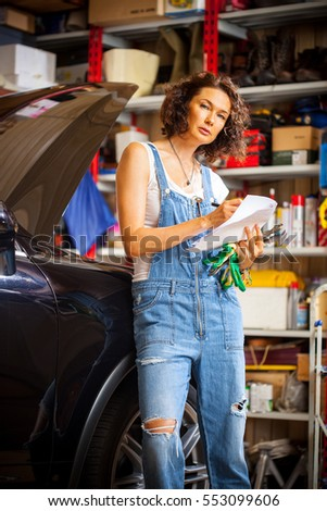 beautiful woman mechanic in blue overalls makes recording near of the car with open hood in the garage