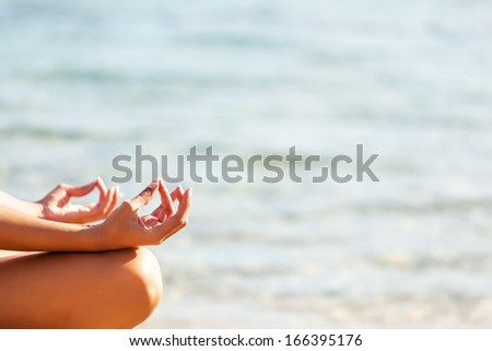 Beautiful woman meditating at the beach.Copy space - stock photo