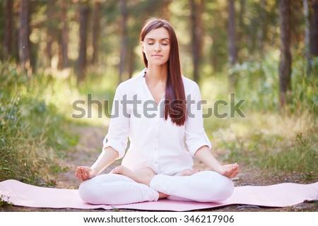 Beautiful woman meditating in nature - stock photo