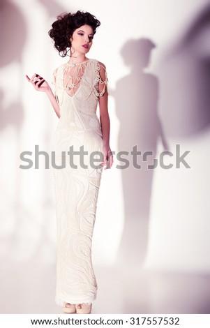 beautiful woman model posing in elegant pearl dress in the studio - stock photo