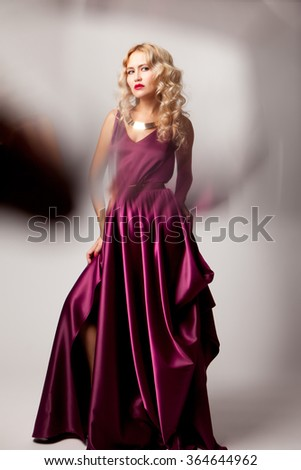 Beautiful woman model posing in elegant purple silk dress with frame of reflection in the studio