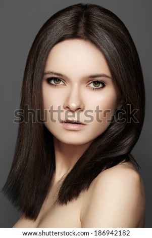 Beautiful woman model with perfect dark hair style, natural eye make-up and pale lips, clean skin on grey background  - stock photo