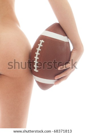 Beautiful woman nude buttocks holding an American Football ball isolated over white background - stock photo