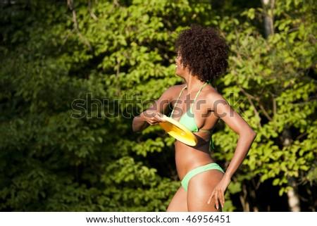 Beautiful woman of African-American origin throwing a Frisbee disc - stock photo