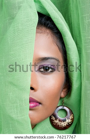 beautiful woman of east indian descent looks from behind a green curtain - stock photo
