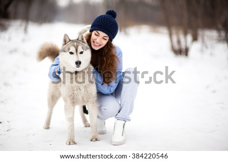 Beautiful woman of twenty-five years old walk in park in winter with dog Husky two years old