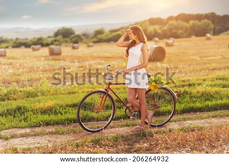 Beautiful woman old bicycle with flowers in wheat field  - stock photo