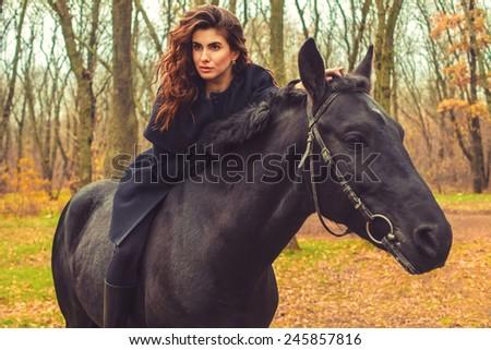 Beautiful woman on a black horse - stock photo