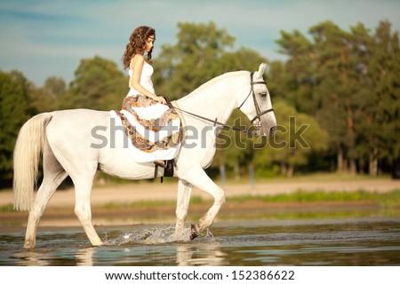 Beautiful woman on a horse. Horseback rider, woman riding horse on beach. - stock photo